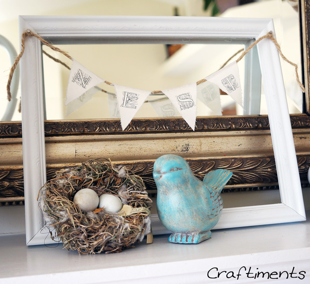 Craftiments:  Miniature fabric and twine bunting strung across a picture frame, a bird and her nest of eggs