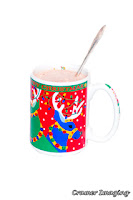 Photograph of a colorful Christmas-themed mug of hot chocolate with a spoon by Cramer Imaging