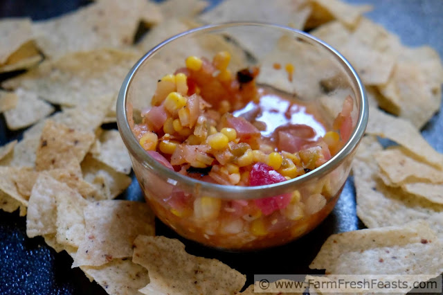 a dish of roasted corn and Hatch chile salsa surrounded by tortilla chips