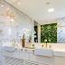 Banheiro marmorizado branco e dourado com banheira, jardim vertical e tv!