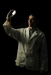 A posed photo of D.J. Bradshaw looking at a petri dish.