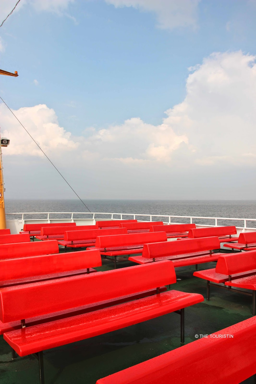 Rows of red benches on the upper green painted deck of a passenger ferry.