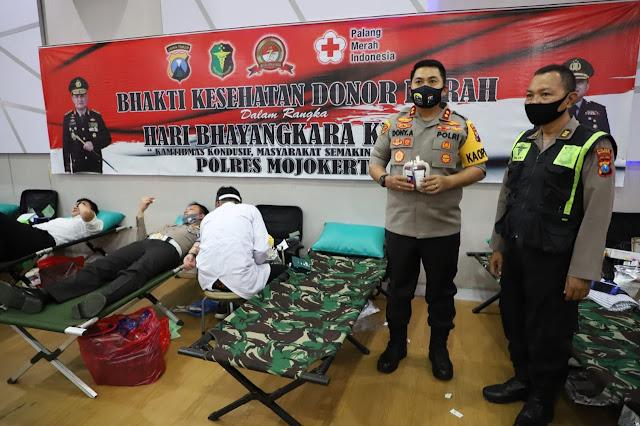 "Mojokerto, Kapolres Mojokerto, AKBP Dony Alexander dan sejumlah anggotanya mengikuti bakti sosial (Baksos) donor darah yang digelar PMI di aula Polres Mojokerto, Senin, (22/06/2020).  Kegiatan kemanusiaan ini dilakukan untuk menjaga pasokan darah PMI di tengah wabah virus corona sekaligus dalam rangka peringatan hari Bhayangkara ke 74 di tahun 2020 kali ini.  Tak hanya anggota Polres Mojokerto dan ASN saja yang turut serta mendonorkan darahnya, tetapi juga nampak anggota TNI dari Kodim 0815 Mojokerto, dari Batalyon Infantri Para Raider 503 Mayangkara termasuk anggota Bhayangkari Cabang Kab. Mojokerto juga turut serta.  Donor darah sebagai wujud kepedulian Polri terhadap sesama terlebih dalam rangka memperingati hari Bhayangkara  ke 74 dan menunjang ketersediaan  stok darah di PMI Kab. Mojokerto bagi masyarakat yang membutuhkan, terang Kapolres usai melaksanakan donor darah.  Dengan bekerjasama dengan PMI Kab. Mojokerto berupaya membantu dengan berpartisipasi dalam kegiatan Bakti Kesehatan Donor Darah Dalam Rangka Hut Bhayangkara Ke 74 kali ini, setidaknya ada kurang lebih 355 personil yang turt mendonorkan darahnya hari ini.  Kegiatan donor darah seperti ini sebenarnya secara rutin sering dilakukan oleh Polres Mojokerto, apalagi pada saat peringatanhari besar nasional dan selalu melibatkan personil Poles Mojokerto.  Kapolres berharap kedepanya kegiatan-kegiatan sosial semacam ini bisa sering dilakukan tentunya dengan sinergitas antara TNI Polri maupun dengan unsur pemerintah daerah.  ""Setetes darah yang disumbangkan sangat berarti bagi saudara-saudara kita yang membutuhkan,"" pungkas Kapolres. (Jayak)"