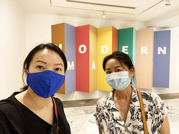 Solo Lisa and her friend pose in front of a sign that says 'Modern' with masks on.