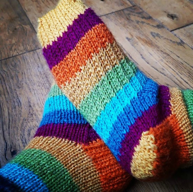 A photo of a pair of feet resting against each other so that you can see the sole of the right foot which is knitted in reinforcing heel stitch.  The sock yarn is stripes of yellow, maroon, dark blue, light blue and green.  The feet are resting on a wooden floor.