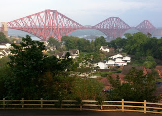 View of the Forth Bridge, lit by the setting sun, from beneath the Forth Road Bridge, North Queensferry, Scotland