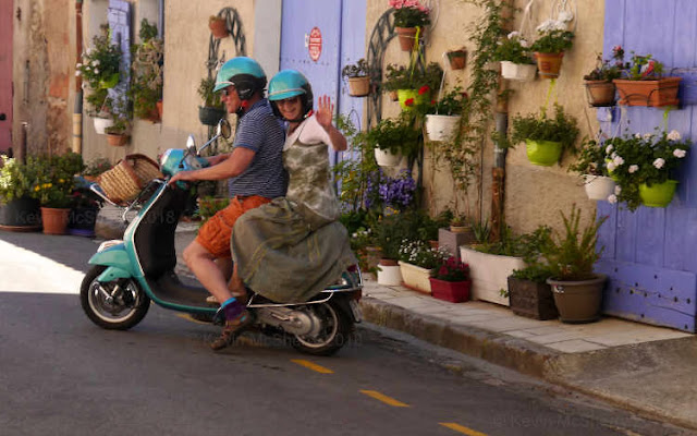 Happy Cotignac couple two-up on a Vespa in a flower-filled sunny Provençal street