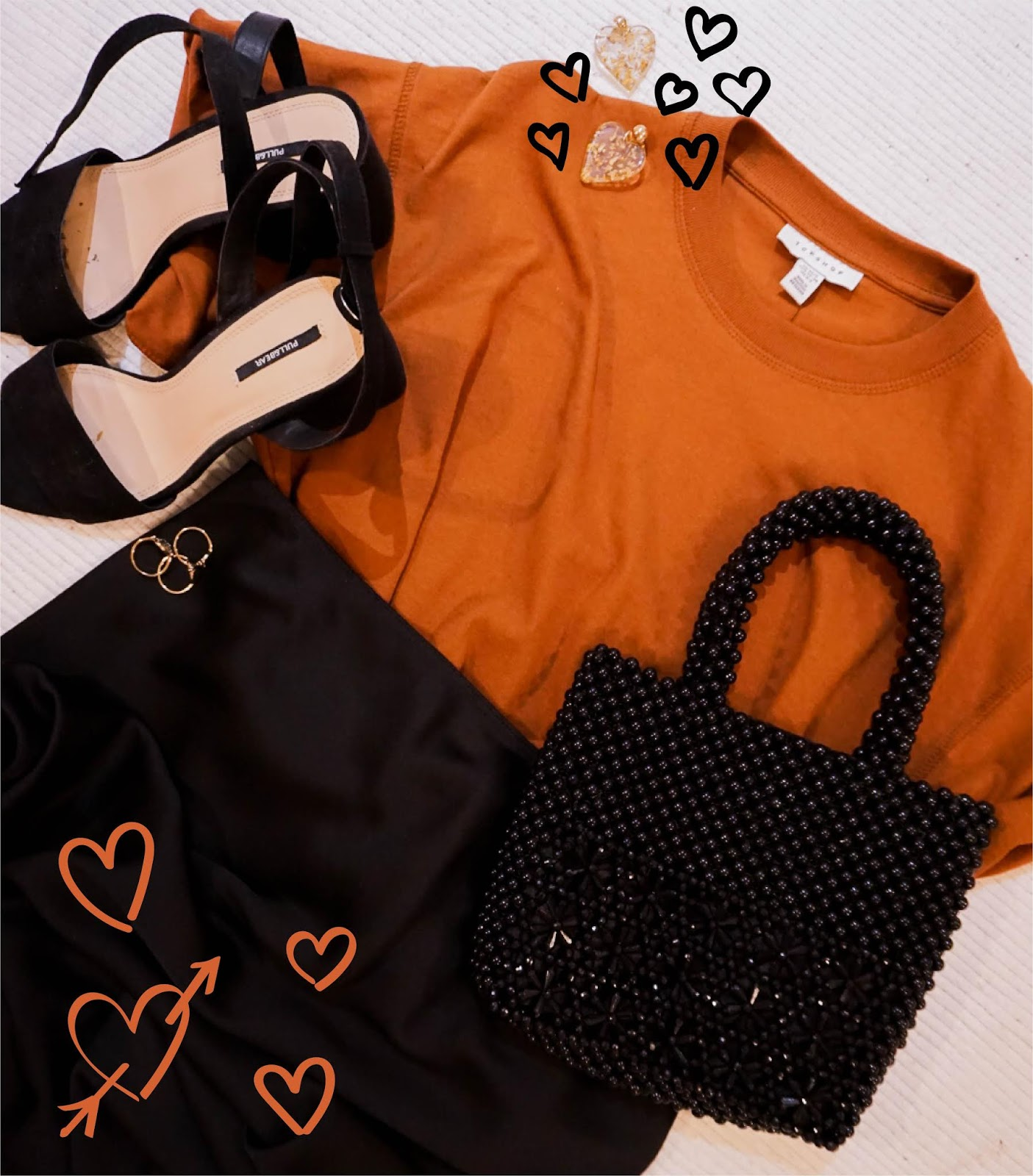 valentines day outfit: orange t-shirt, statement gold heart shaped earrings, black beaded bag, black midi satin skirt, gold rings, black heeled sandals