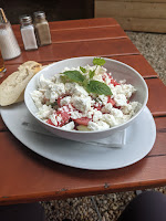 a photograph of a salad bowl with a layer of cucumbers topped with a layer of watermelon, all topped with a heap of crumbled feta and a sprig of mint
