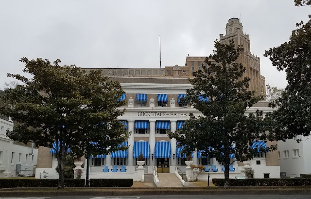 old three-story building with blue awnings on the windows