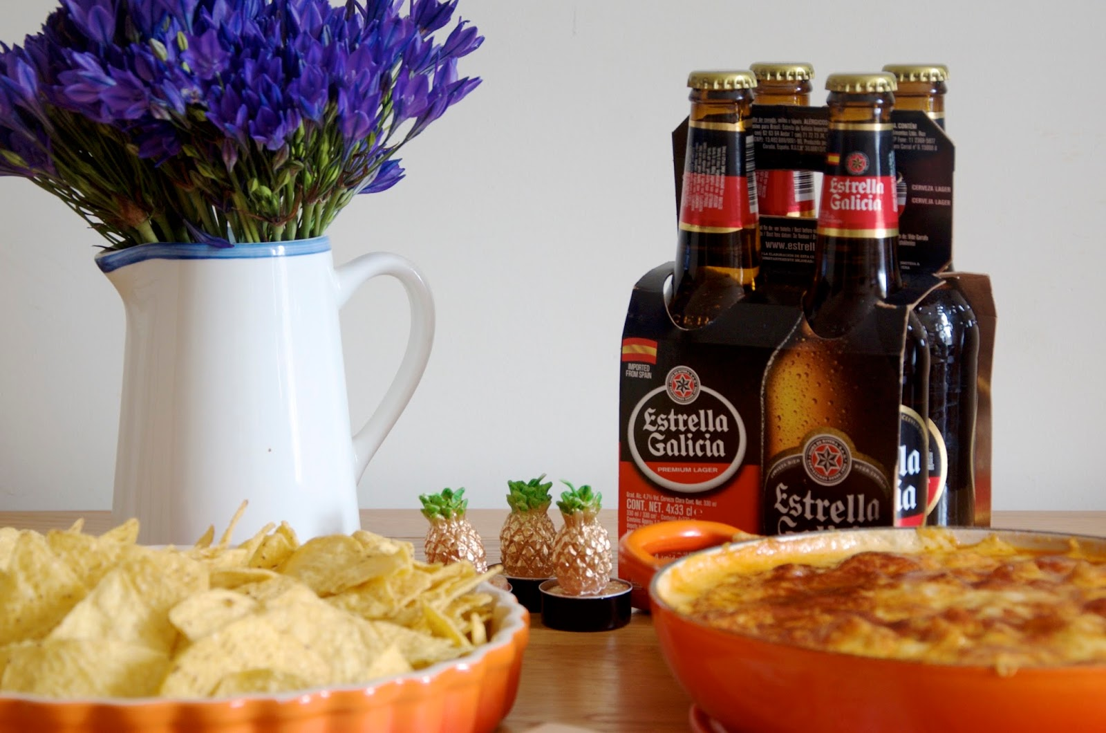 Buffalo Chicken Dip in le creuset casserole, estrella galicia beer, pineapple candles and purple flowers
