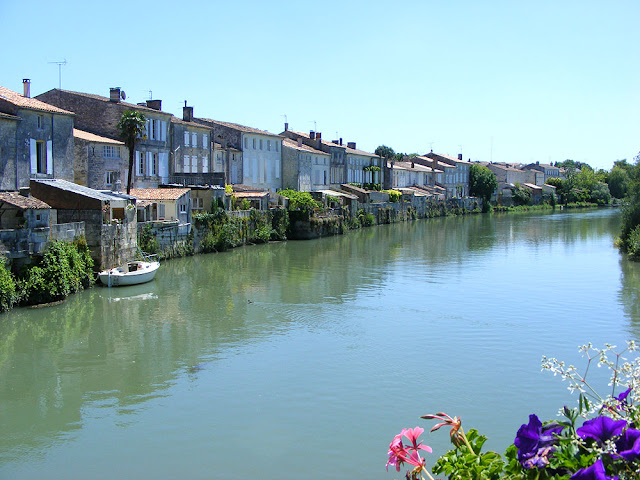 Houses backing on to the Charente in Saint Savinien. France. Photographed by Susan Walter. Tour the Loire Valley with a classic car and a private guide.