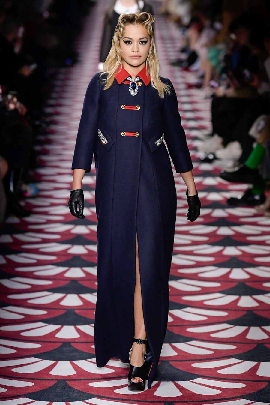 Rita Ora looks sensational in a navy jewel-embellished military jacket as she struts down the catwalk