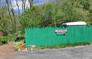 "a bright teal fence with a sign reading ""Children's Garden"" provides the entrance to the childrens garden at Lauritzen Gardens"