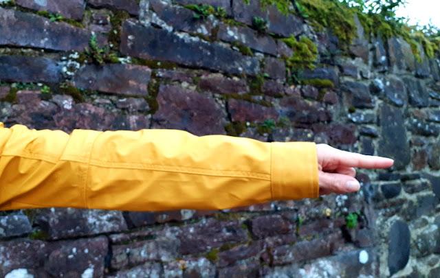 Keltainen sadetakki, kivimuuri, sormet