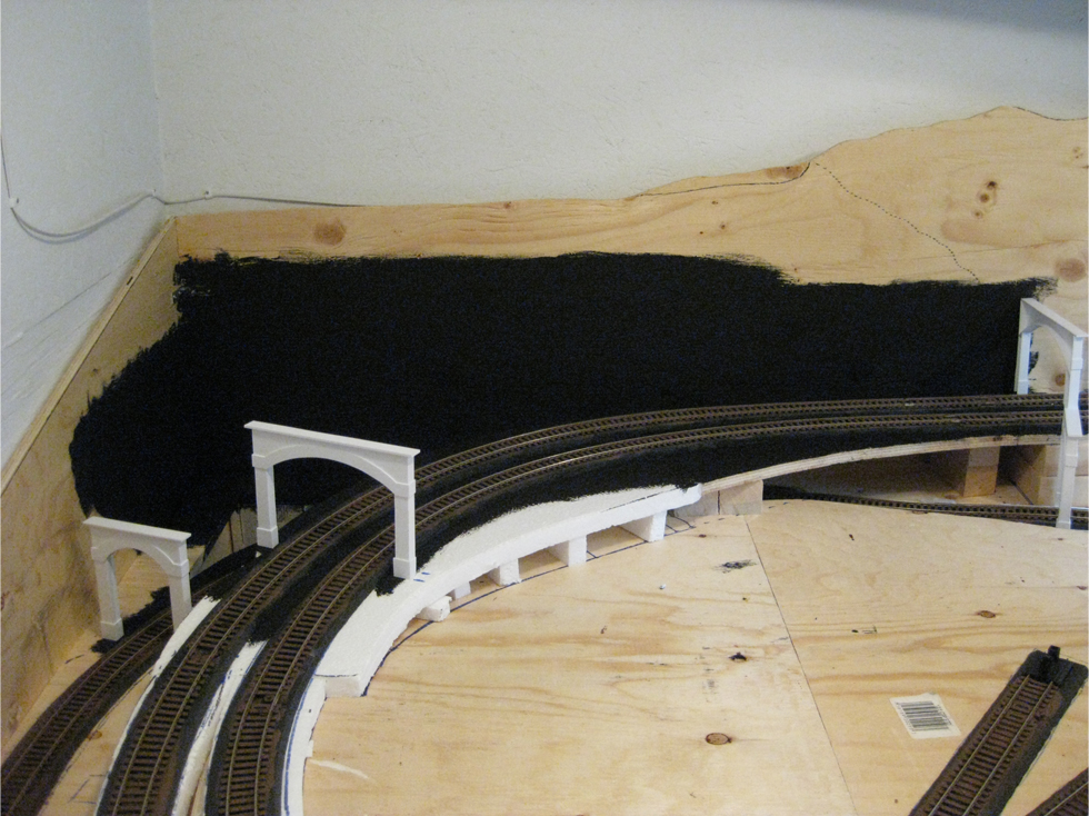 Benchwork and foam painted black around track in the location of the future tunnel