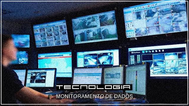 Imagem ilustrativa de funcionário do governo monitorando dados através de inúmeros monitores de computador.