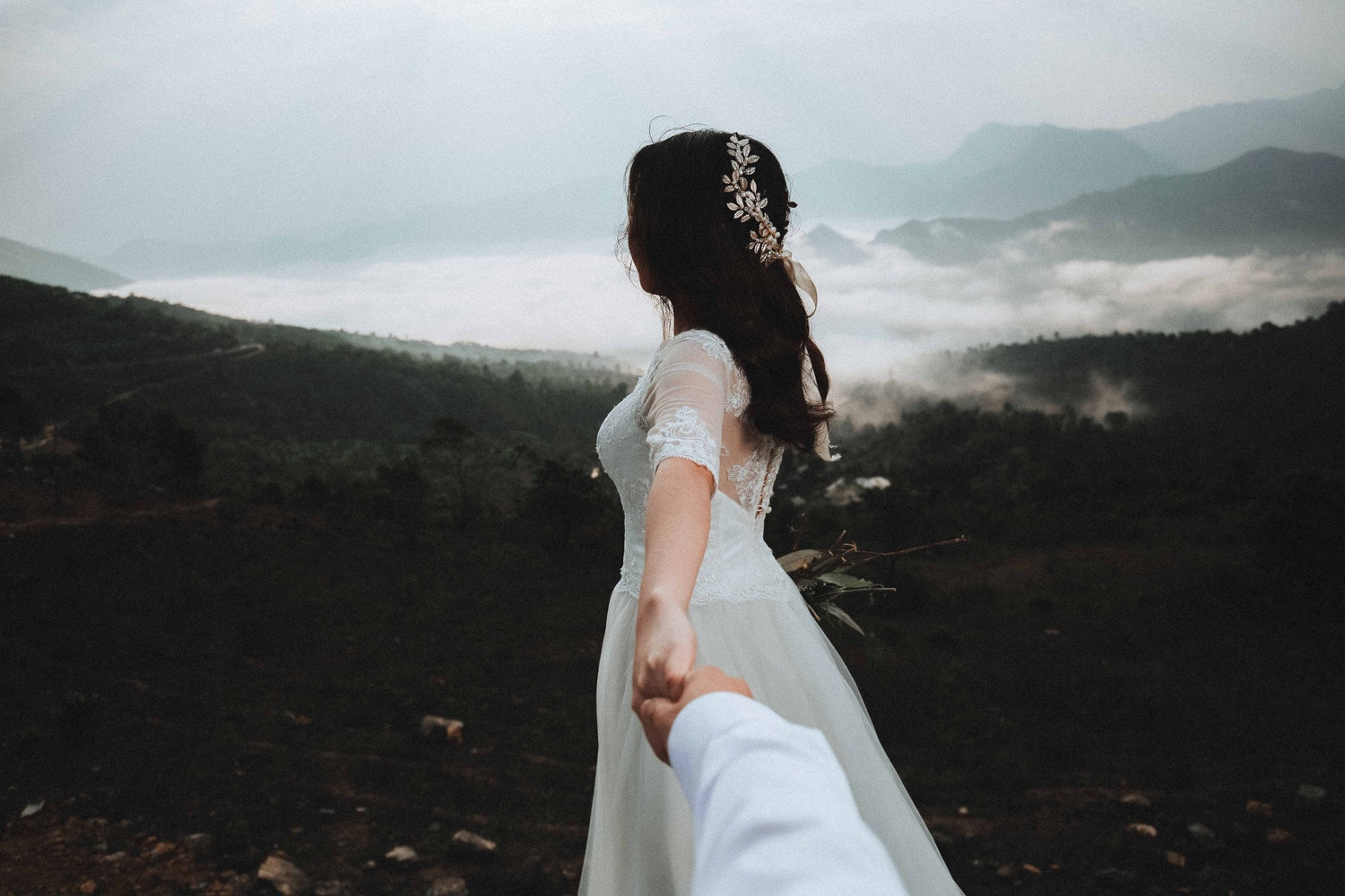 beautiful bride in a wedding dress holds the hand of her future husband