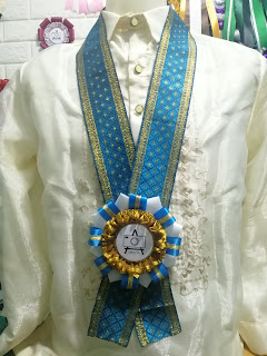 A Blue and Gold Rosette with Blue and Gold Lei for Special Guests worn in a Barong Tagalog