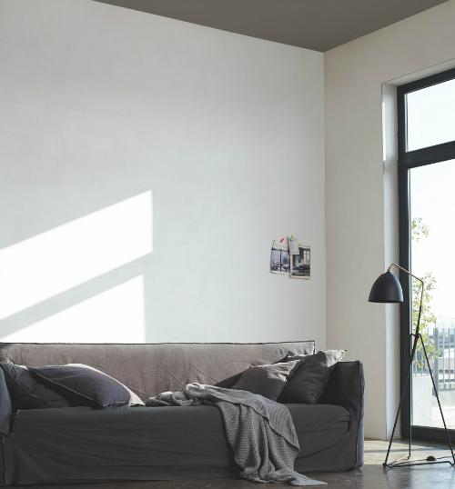 In einem Wohnzimmer sind die Wände weiß, aber die Decke grau gestrichen
