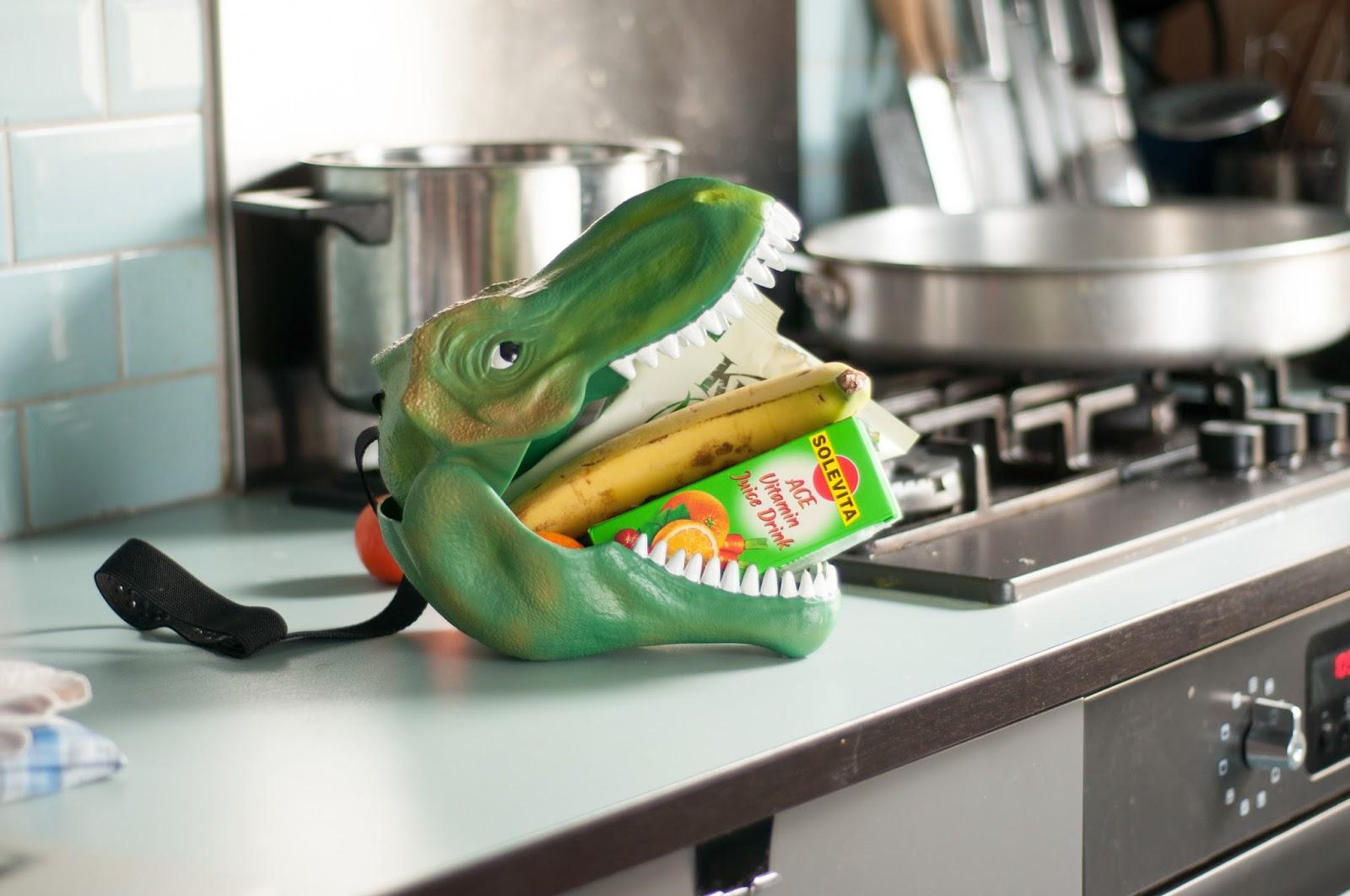 Eine Lunchbox in Form eines T-Rex Dinosaurier Kopf liegt auf einem Küchentisch im Hintergrund sieht man Töpfe