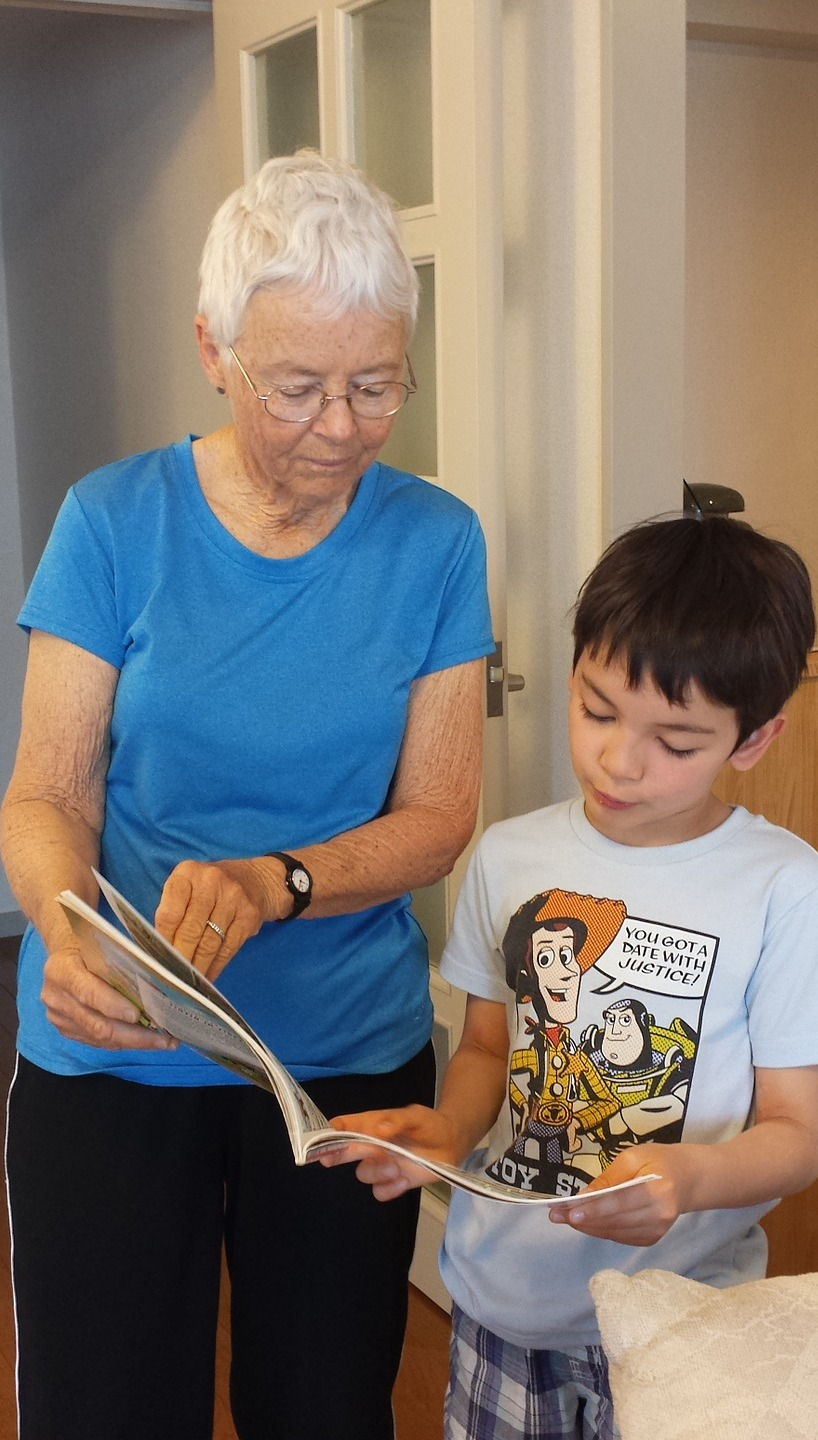A grandmother reading a book with grandson.