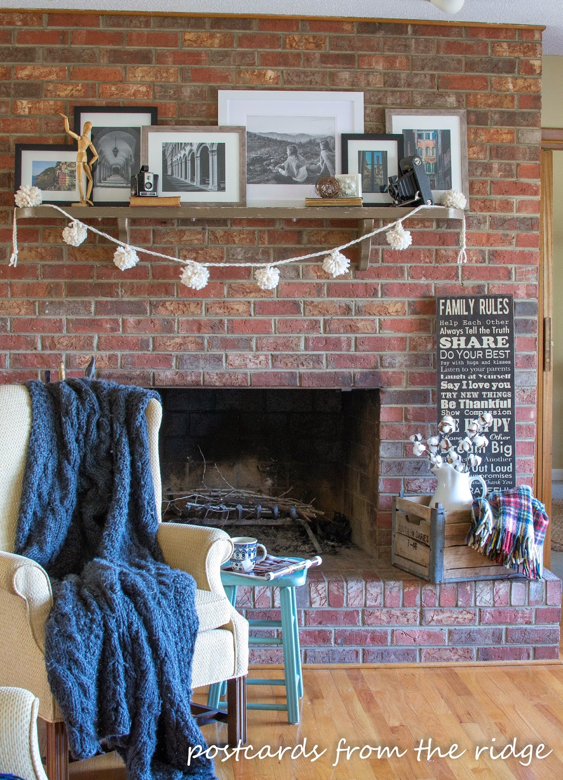brick fireplace with yarn pom poms