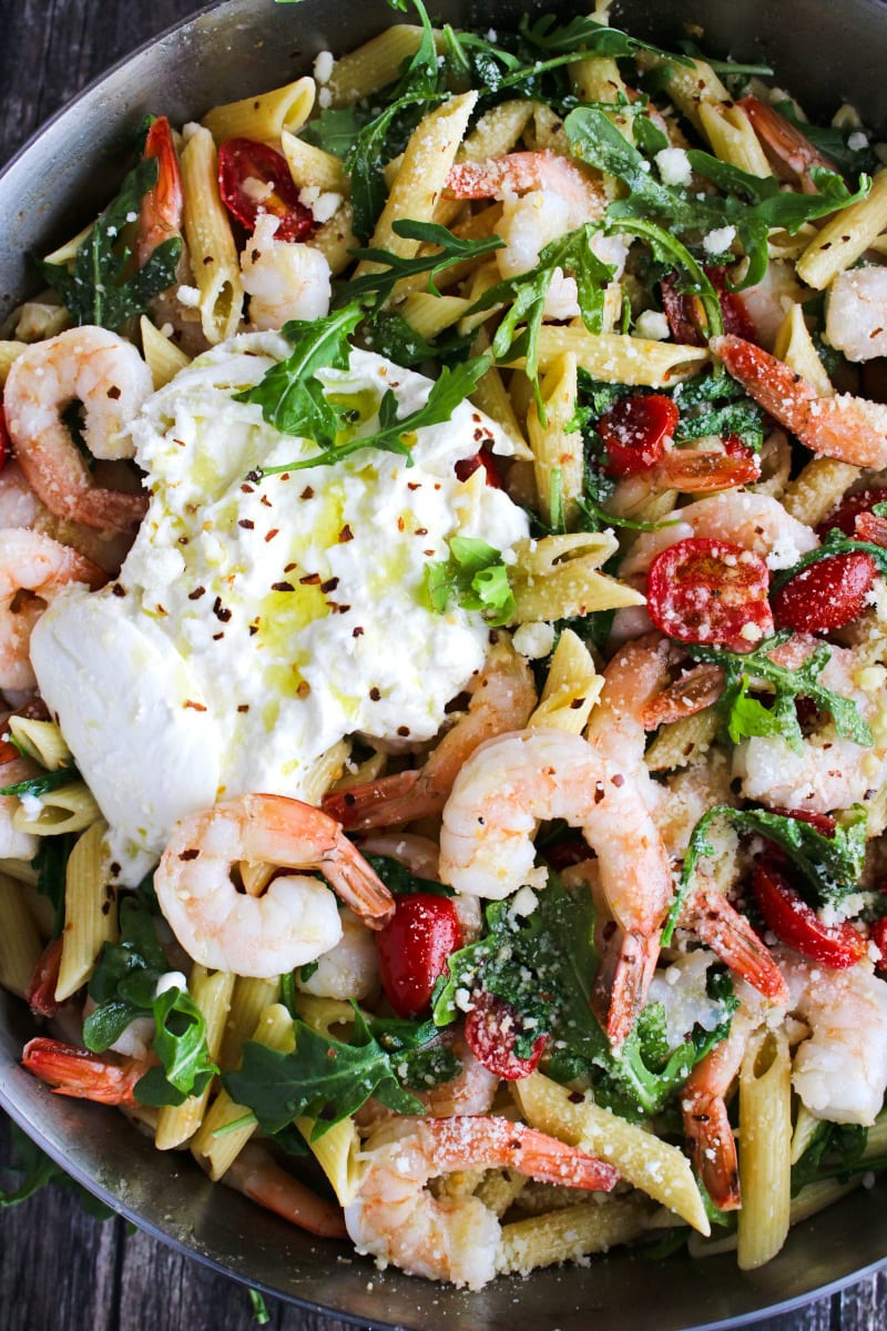 Top view closeup of Shrimp, Arugula, and Burrata Pasta in a stainless steel skillet.