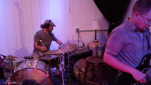 picture of man behind drums with a mixing board