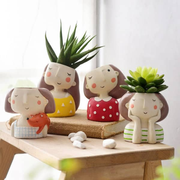 shy girl face planters containing a flower or plant in each one