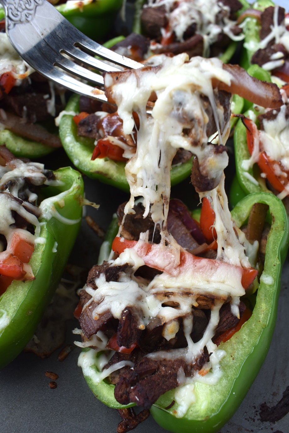 cheesy bite of Philly cheesesteak stuffed peppers