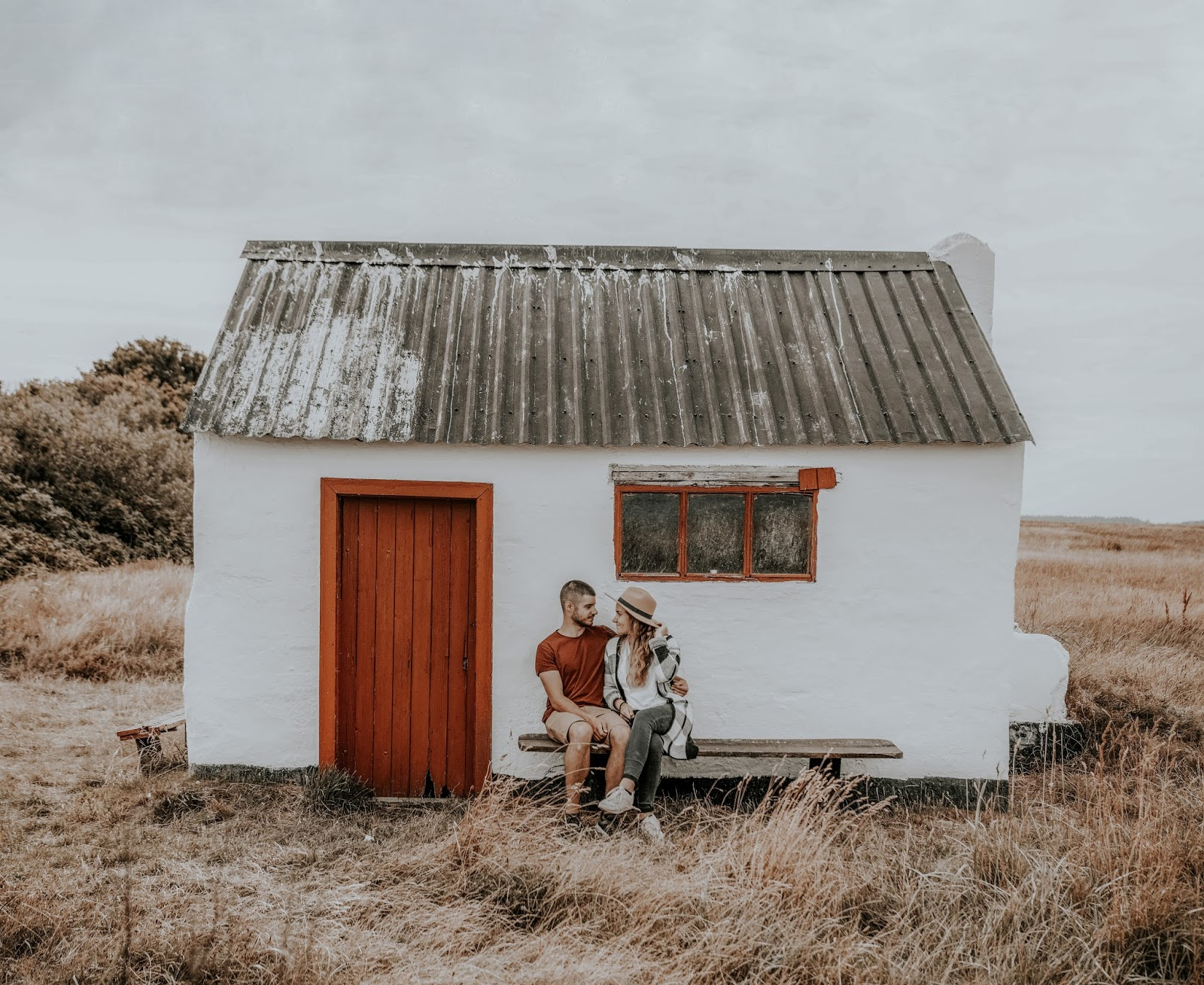 Biała chata w stylu skandynawskim. Para siedząca przed domem na ławce