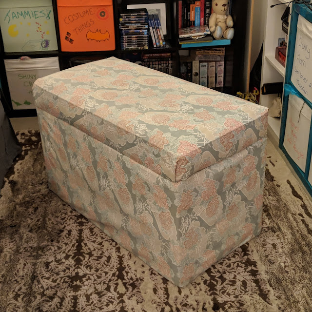A photo of a loungeroom lined by shelving, the forefront of the photo is an ottoman covered in very faded fabric, which would have once been pink flowers on a blue background. The fabric is dirty and evidently a home job.