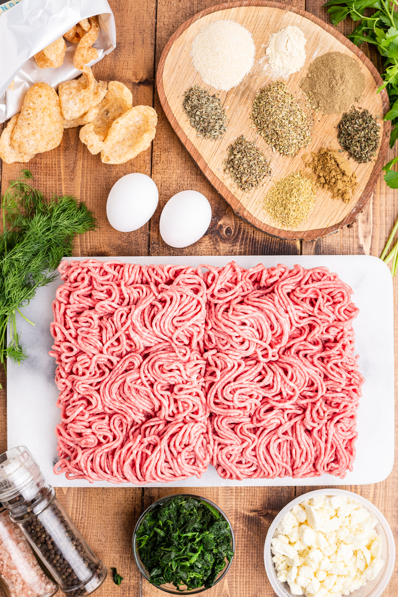 Photo of the ingredients needed to make Keto Greek Style Meatloaf on a wooden table.