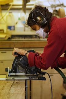 Woman using a circular saw.