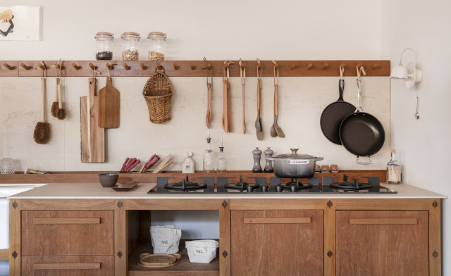 galley kitchen with long wood peg rack for hanging kitchen utensils, pans, and hanging baskets