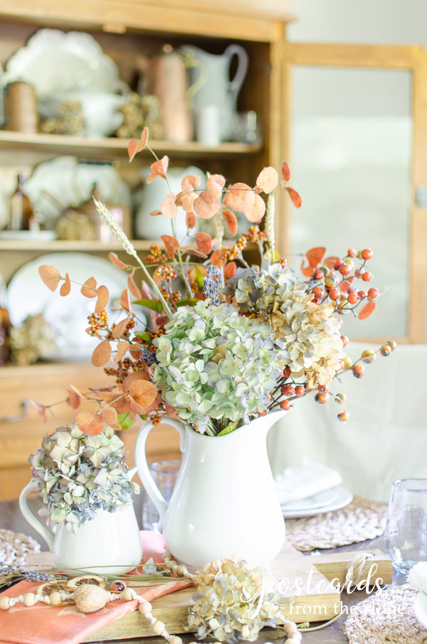 white stoneware pitcher with soft fall colors and flowers