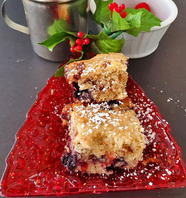 a little red christmas tree plate with banana cranberry bars in it there is powdered sugar on top