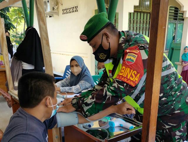 Babinsa Yudi Teguh Membantu Tim Nakes Puskesmas Tanjung Melakukan Vaksinasi kepada Mayarakat