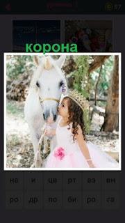 девочка в короне целует белую лошадь