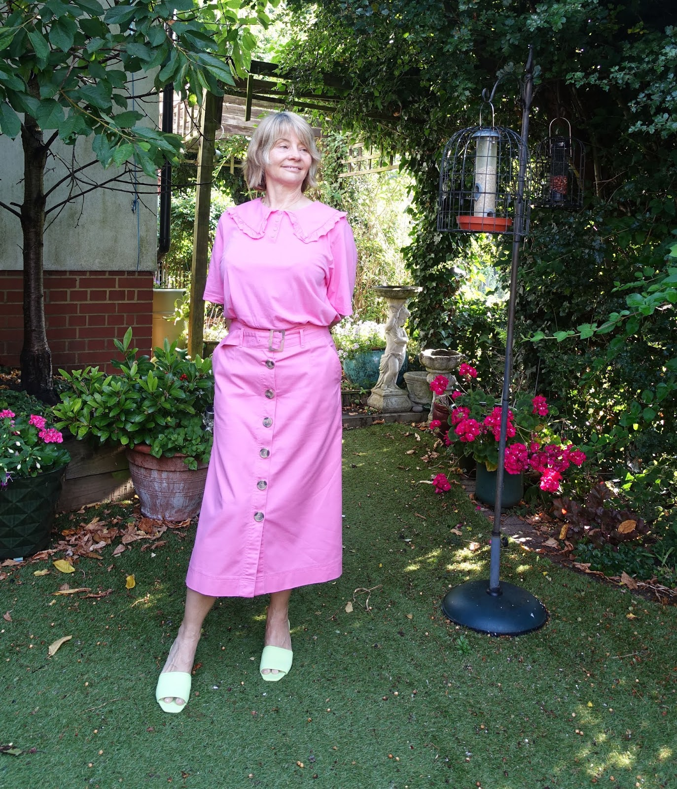 A chic look for the over-50s with a waist defining A line skirt and statement collar top, both in pink which flatters the complexion, and lime green mules for a pop of color. As worn by Is This Mutton blogger Gail Hanlon