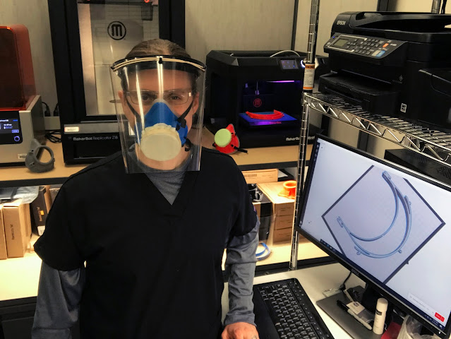 """Elizabeth """"Betsy"""" Weissbrod stands in PPE gear with the 3D printing equipment"""