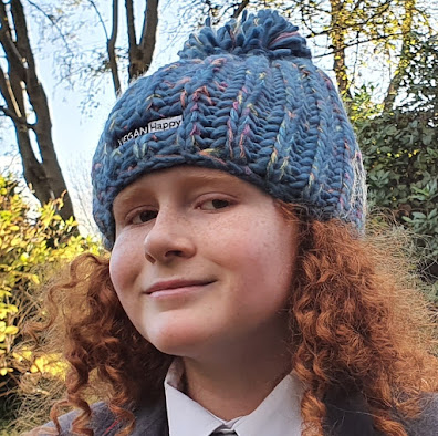 Smiley redhaired boy wearing a Vegan happy aurora pompom beanie outdoors in Autumn