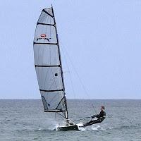 Bir yelkenlide trapez yaparak tekneyi dengede tutan sporcu