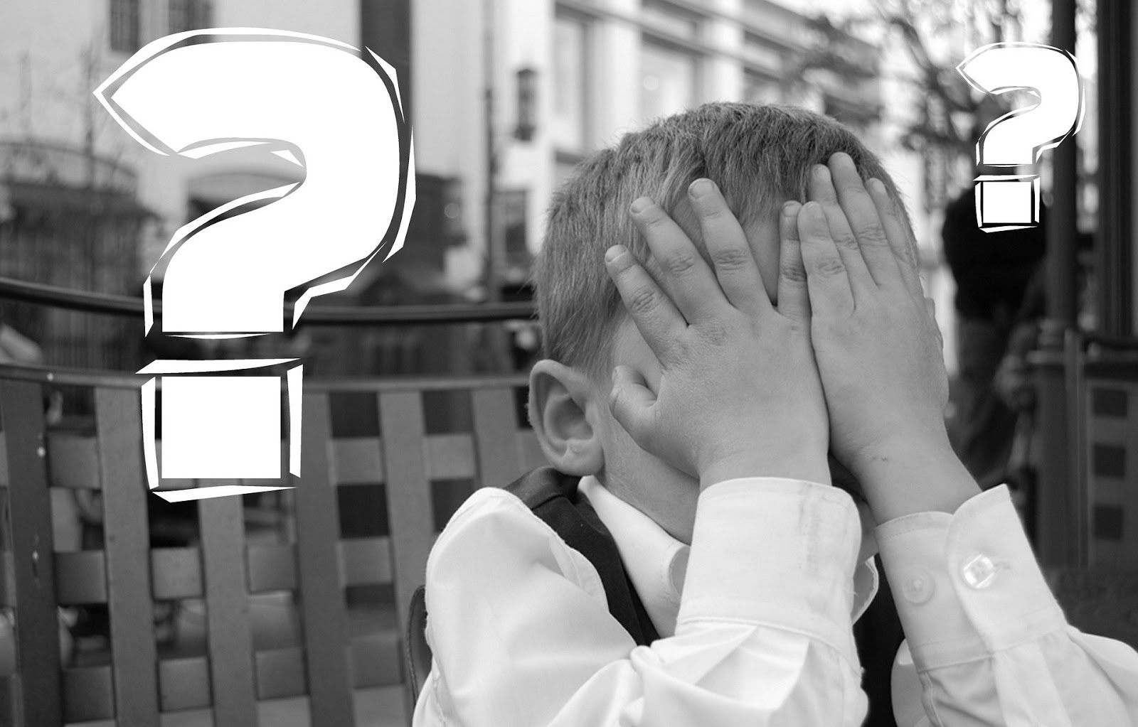 a young boy sits with his hands covering his face and two white question marks surround him to illustrate a blog post about inaccurate war movies