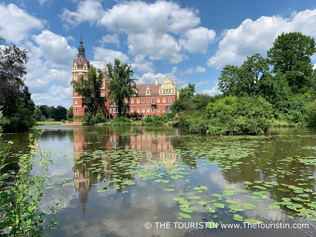Water lilies on a lake in front of a red-ish coloured renaissance castle under a blue sky with fluffy clouds.