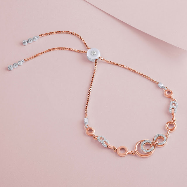 Gold necklace shot flatlay-style on a pastel pink surface.