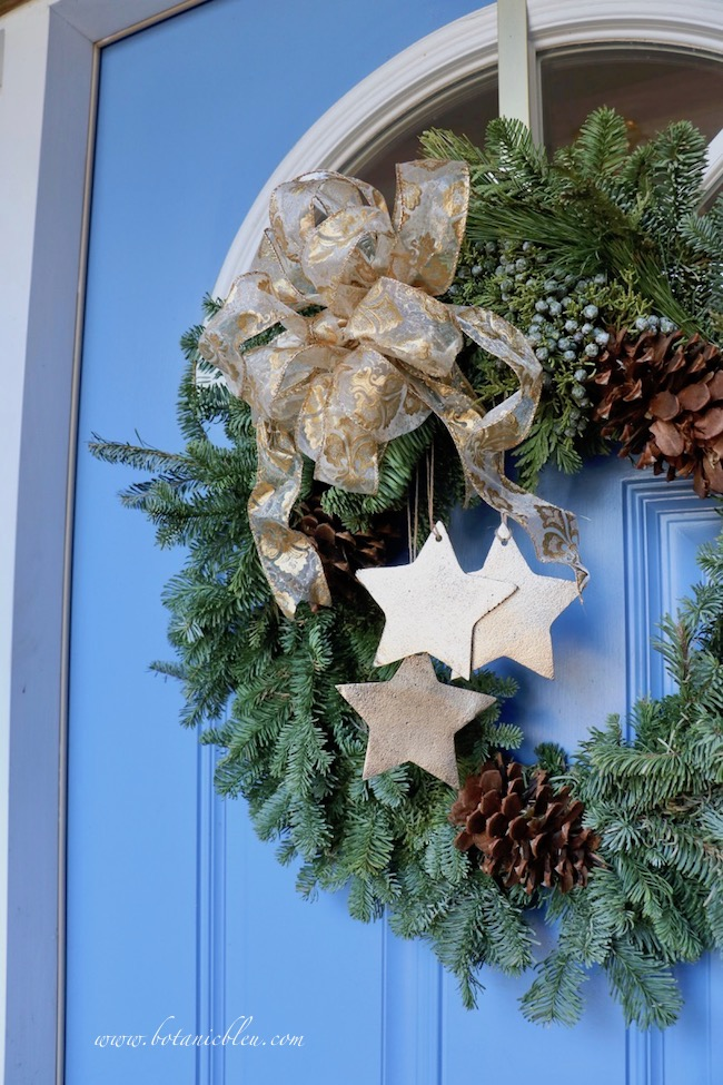 Tips for best ever Christmas wreath with stars on blue front door