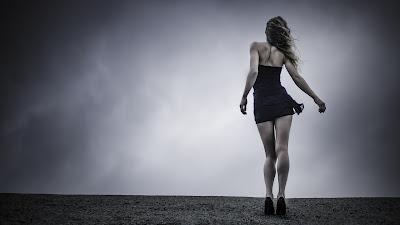 Chica vestida de negro andando en la nada