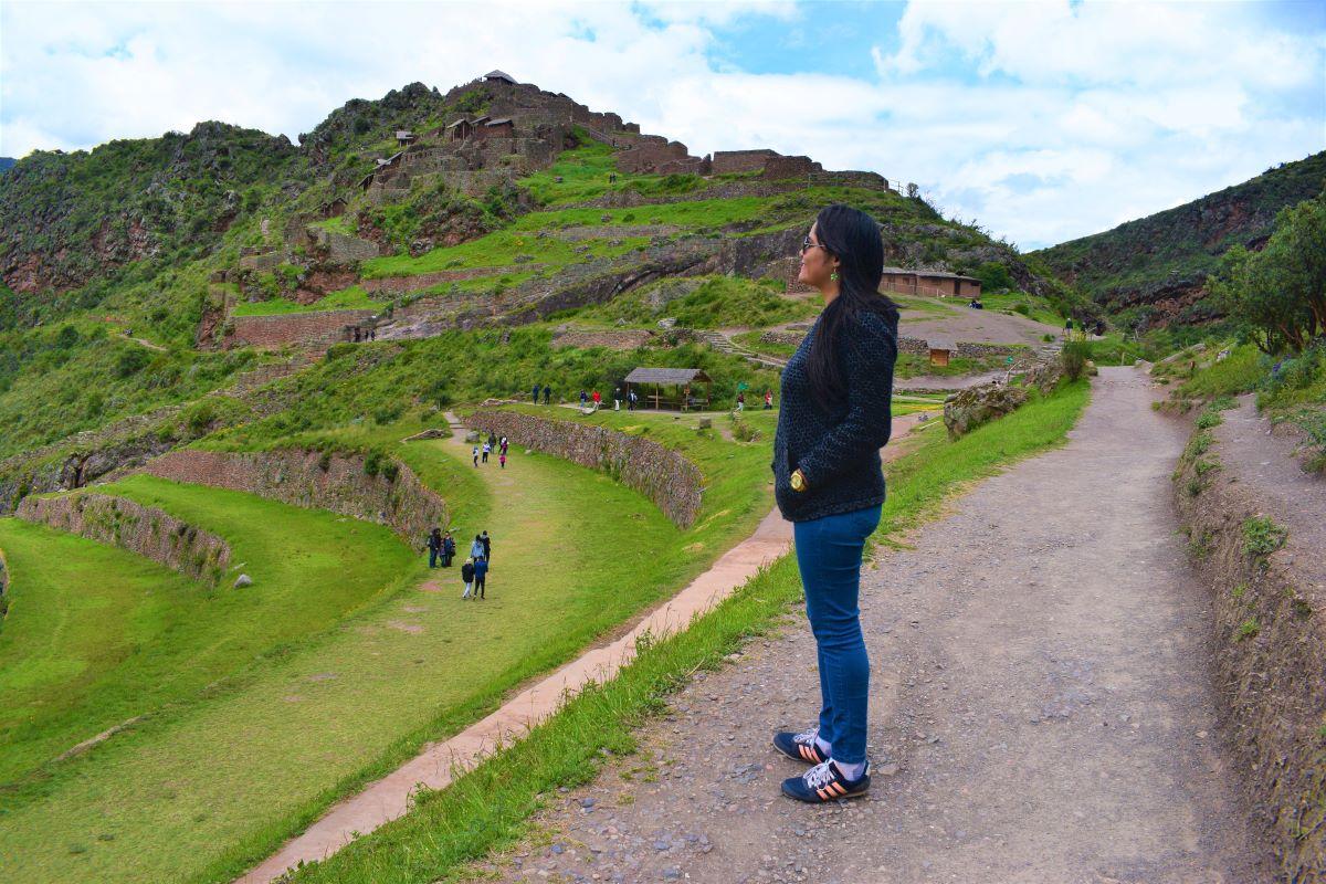 mulher jovem olhando um sitio arqueológico inca no peru